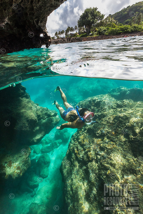 A woman snorkels at Shark's Cove on the North Shore of O'ahu.