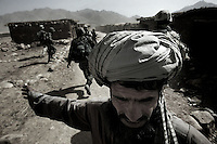 a store keeper from  a bazar is being searched by first platoon, battle company, 2nd battalion, 503d regiment, 173d airborne brigade, US AMRY soldiers during a raid in the Larzab District, zabul province, afghanistan on september 13 2005..firts platoon landed on sept 12 in the village of Hazarbuz in the Kanagh Ghar district. during the search thet found a small stash of weapons hidden in a compoud. the next morning third squad was sent on a mountain top to search for talibans. in the afternoon the platoon was moved  to the Wakil Kor district. during a search in a bazar they destroyed to motorcycles, illegal in the Zabul province. the platoon then initiated a 15 km movement towards bayolugh FOB, their base in  the Dey Chapon valley arriving before sunset.
