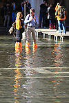 Tourists walk with plastic bags to protect their shoes on flooded streets during an acqua alta (high-water). The Acqua Alta, a convergence of high tides and a strong sirocco, reached 125 centimetres in Venice, on November 20, 2013.  <br /> <br /> &copy; Pierre Teyssot