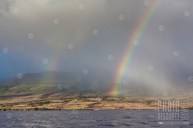 Rainbow over Maui mountains with leeward coast and ocean in the foreground.