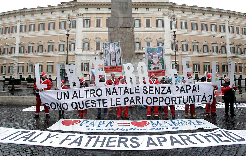 "I padri separati protestano vestiti da Babbo Natale per i loro diritti davanti a Montecitorio, Roma, 21 dicembre 2012..Separated fathers rights activists wearing Santa Claus costumes hold letters forming the word ""Free them"" and a banner reading ""Another Christmas without dad. Are these equal opportunities?"" during a protest in front of the Lower Chamber in Rome, 21 December 2012..UPDATE IMAGES PRESS/Riccardo De Luca"