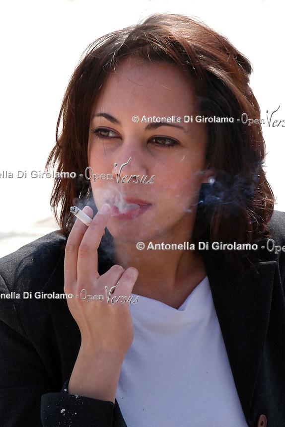 Ragazza mentre fuma una sigaretta. Girl is smoking a cigarette....