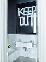 """The guest bathroom has a bath and washbasin by Barber Wilsons & Co. The vanity mirror above, spray-painted with the words """"Keep Out."""", is a conceptual art piece by the artist Rashid Johnson."""