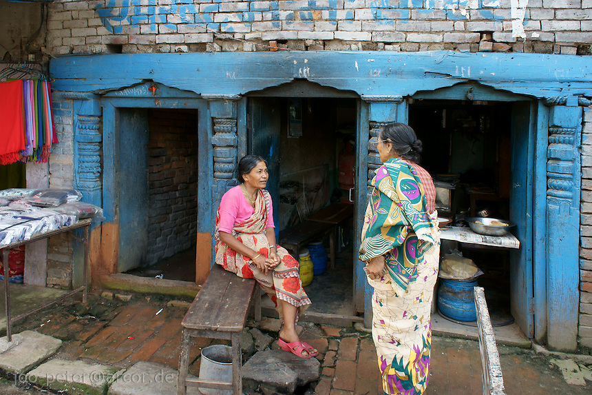 Newar women talking in front of a food place in Bhaktapur, Nepal, brikcstone building, wooden front part painted blue