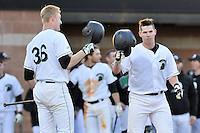 Catcher Jordan Miller (33) of the University of South Carolina Upstate Spartans, right, is congratulated by Charlie Carpenter (36) after hitting a solo home run in the seventh inning of a game against the George Mason Patriots on Friday, February 19, 2016, at Cleveland S. Harley Park in Spartanburg, South Carolina. (Tom Priddy/Four Seam Images)