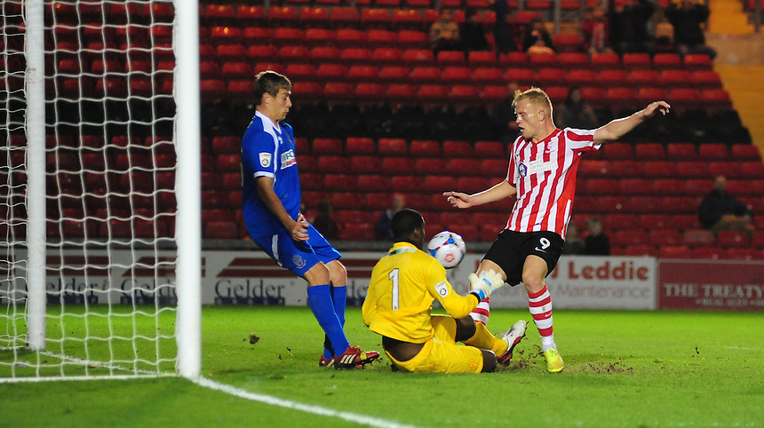 Alfreton Town's Anthony Howell, who was forced to play in goal for the FA Cup Fourth Qualifying round replay, forces Lincoln City's Jordan Burrow to scoop his shot over the crossbar<br /> <br /> Photo by Chris Vaughan/CameraSport<br /> <br /> Football - FA Challenge Cup Fourth Qualifying Round replay - Lincoln City v Alfreton Town - Tuesday 28th October 2014 - Sincil Bank - Lincoln<br /> <br /> &copy; CameraSport - 43 Linden Ave. Countesthorpe. Leicester. England. LE8 5PG - Tel: +44 (0) 116 277 4147 - admin@camerasport.com - www.camerasport.com