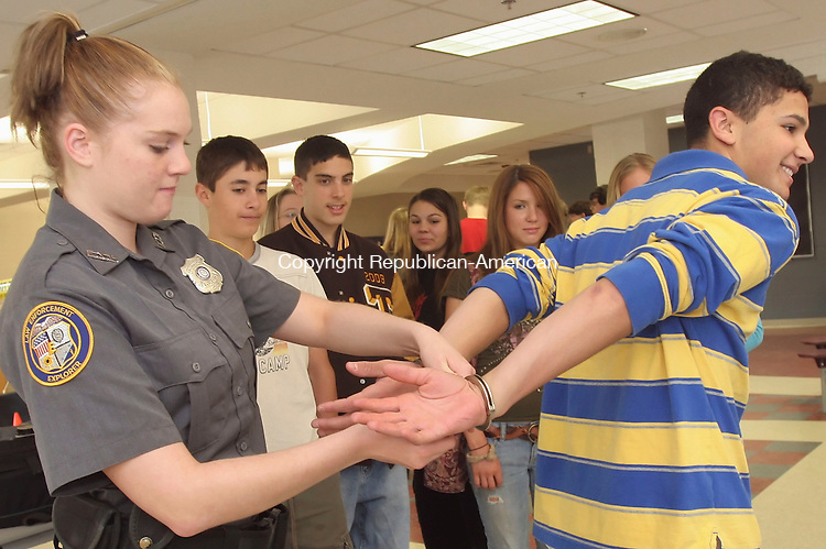 THOMASTON, CT-17 May 2006-051706TK01- (left to right) The Thomaston Police Explores Post 4343 held a workshop Wednesday to demonstrate learned police enforcement skills. Adam DeNapoli, Thomaston High School junior, volunteers to assist Kaitlyn York in a demonstration on the correct procedure for handcuffing and removing handcuff from a subject. Tom Kabelka Republican-American (Thomaston Police Explores Post 4343, Adam DeNapoli, Kaitlyn York)