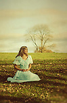 Beautiful woman in vintage dress sat on the grass