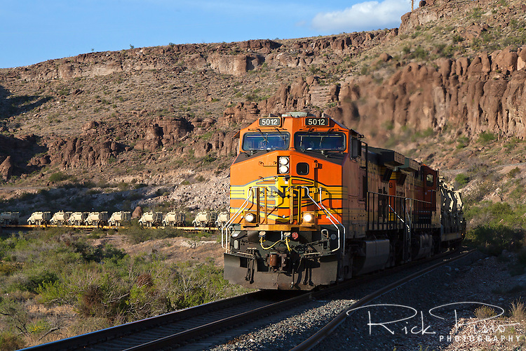 BNSF 5012, a GE C44-9W locomotive,  leads a westbound freight of BAe Caiman armored vehicles through Sawmill Canyon west of Kingman, Arizona.