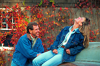 Couple laughing with fall foliage in background