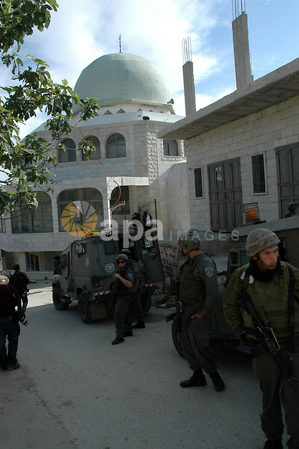 """Israeli troops stand outside the Bilal Ibn Rabah mosque in the West Bank village of Hawara, near the West Bank city of Nablus, on April 14, 2010. Israeli settlers desecrated a mosque and set fire to two cars in the occupied West Bank, Palestinian security officials said. The Israeli army confirmed that """"anonymous suspects"""" scrawled graffiti, including a Jewish star of David alongside the name of the Prophet Mohammed written in Hebrew.  Photo by Nedal Shtieh"""