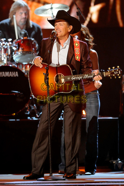 GEORGE STRAIT .performs during the 43rd Annual CMA Awards, Country Music's Biggest Night, held at the Sommet Center, Nashville, Tennessee, USA, 11th November 2009. live show on stage full length concert gig music  microphone guitar cowboy hat brown jacket .CAP/ADM/LF.©Laura Farr/AdMedia/Capital Pictures.