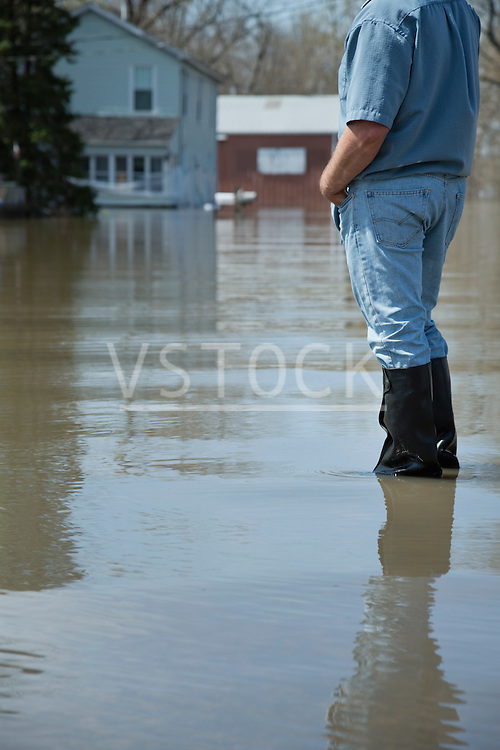 Man standing with hands in pockets looking at flooded street