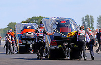 Aug. 16, 2013; Brainerd, MN, USA: Crew members push the car of NHRA funny car driver Blake Alexander towards the starting line during qualifying for the Lucas Oil Nationals at Brainerd International Raceway. Mandatory Credit: Mark J. Rebilas-
