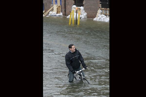 """JLX19. BROOKLYN (ESTADOS UNIDOS), 29/10/2012.- Un hombre intenga circular en bicicleta por una zona inundada en Brooklyn, Nueva York, Estados Unidos, hoy, lunes 29 de octubre de 2012. El huracán """"Sandy"""", que se encuentra a unos 615 kilómetros al sudeste de la ciudad de Nueva York, sigue ganando fuerza y se espera que traiga una marejada ciclónica junto con vientos de fuerza huracanada, informó hoy el Gobierno. EFE/Justin Lane."""