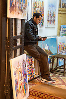 Essaouira, Morocco.  Art Gallery Clerk Checking his cell Phone.