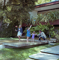 David and Elizabeth Netto and their two daughters playing on the stepping stones of the shallow reflecting pool adjacent to the house