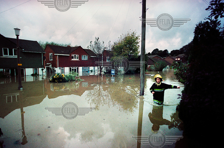 A fireman wades through the floodwaters outside residential housing in Malling (Lewes).