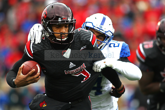 Cornerback Blake McClain of the Kentucky Wildcats sacks quarterback Reggie Bonnafon during the first half of the game against the Louisville Cardinals at Papa Johns Cardinals Stadium on Saturday, November 29, 2014 in Louisville, Ky. Louisville leads Kentucky 21-13. Photo by Michael Reaves | Staff