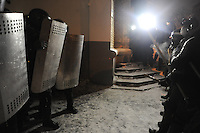 An armed group of protesters faces a deplyment of riot police with shields during the night. Kiev. Ukraine