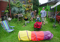 A young local mother, father and toddler son play in their yard, with a barbecue starting and toys scattered about, Big Island.