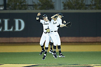 Wake Forest Demon Deacons outfielders Chris Lanzilli (24), Wyatt Beddow (7), and Michael Ludowig (22) celebrate their season opening win over the Sacred Heart Pioneers at David F. Couch Ballpark on February 15, 2019 in  Winston-Salem, North Carolina.  The Demon Deacons defeated the Pioneers 14-1.  (Brian Westerholt/Four Seam Images)