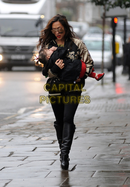 Myleene Klass with daughter Hero.spotted in Highgate, London, England..February 27th, 2013.full length mother mom mum kid child family sunglasses shades black jacket gold embroidered floral print leggings boots holding carrying  .CAP/AOU.©AOU/Capital Pictures.