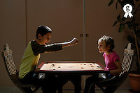 Boy (11-13) and girl (5-7) playing 'Carrom' board game, profile (Licence this image exclusively with Getty: http://www.gettyimages.com/detail/73532487 )