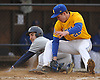 Patrick Hoffman #22, East Meadow pitcher, right, tries to tag Max Braccia #8 of Plainview JFK, who slides home safely in the top of the fourth inning of a Nassau County varsity baseball game at  East Meadow High School on Thursday, March 30, 2017. Plainview JFK won by a score of 4-0.