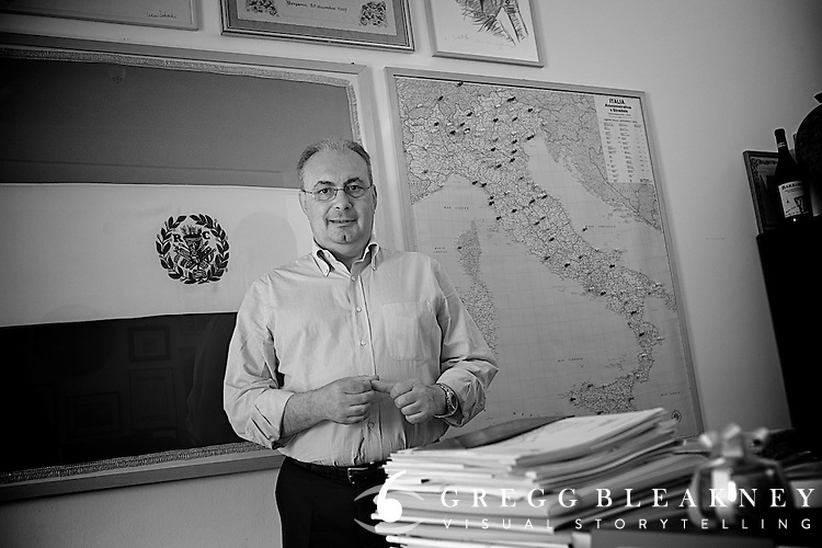 Angelo Zomegnan behind stacks of documents stacked on the meeting desk in his office at the RCS HQ in Milan.
