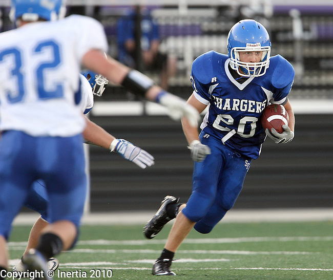 SIOUX FALLS, SD - AUGUST 27:  Andrew DeVaney #20 of Sioux Falls Christian looks for running room as Jacob Berg #32 of Garretson closes in during the second quarter of their game Friday night at the University of Sioux Falls Stadium. (Photo by Dave Eggen/Inertia)