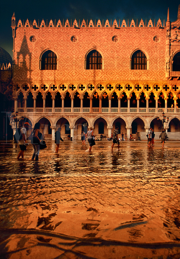 Doges Palace reflected in Piazza San Marco flooded at high tide Venice Italy.