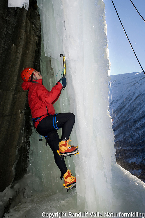 Mann klatrer på innsiden av frossen foss ----- Man climbing on the inside of a frozen waterfall
