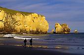 Couple walking on beach near cliff