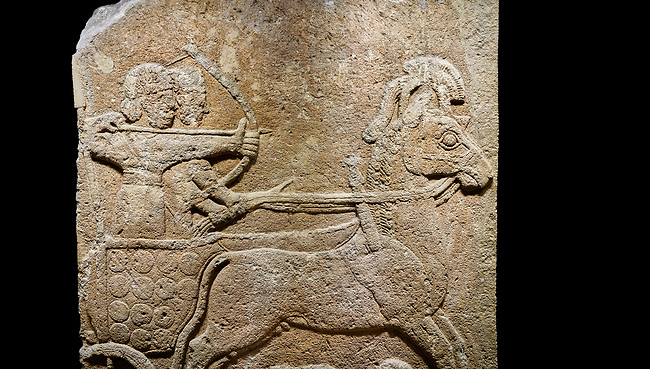 Hittite relief sculpted orthostat stone panel of Long Wall Limestone, Karkamıs, (Kargamıs), Carchemish (Karkemish), 900 - 700 B.C. Anatolian Civilisations Museum, Ankara, Turkey<br /> <br /> Chariot. One of the two figures in the chariot holds the horse's headstall while the other throws arrows. There is a naked enemy with an arrow in his hip lying face down under the horse's feet It is thought that this figure is depicted smaller than the other figures since it is an enemy soldier. The lower part of the orthostat is decorated with braiding motifs.<br /> <br /> On a black background.