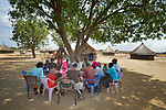Members of a savings group in Panyagor, a village in South Sudan's Jonglei State, meet under a tree to record contributions to their personal accounts. The group includes internally displaced persons and those who have returned from refuge outside the war-torn country.<br /> <br /> The group is supported by the Lutheran World Federation, a member of the ACT Alliance.