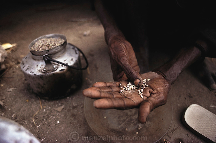 An old woman shows scavenged lentils in her hand in a refugee camp near Merca, 100 km. south of Mogadishu, war-torn capital of Somalia. March 1992.