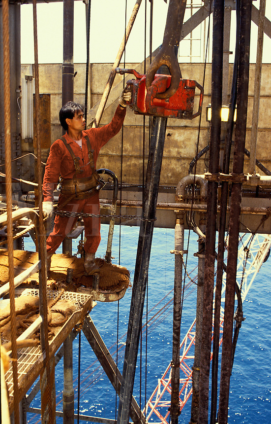 Derrick man at work on offshore oil exploration drilling rig. South China Sea..