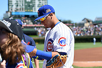 Chicago Cubs second baseman Javier Baez (9) signs autographs before a game against the Milwaukee Brewers on August 14, 2014 at Wrigley Field in Chicago, Illinois.  Milwaukee defeated Chicago 6-2.  (Mike Janes/Four Seam Images)