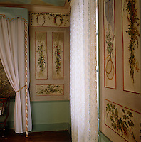 A decorative scheme of painted panels topped with a floral frieze in a child's bedroom in the atelier of 19th century artist Charles Daubigny
