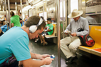 A music listener wears his over the ear headphones in a subway car in New York on Saturday, June 23, 2012. The NYPD has previously reported a spike in subway crime fueled in part part by robberies of electronics. (© Richard B. Levine)