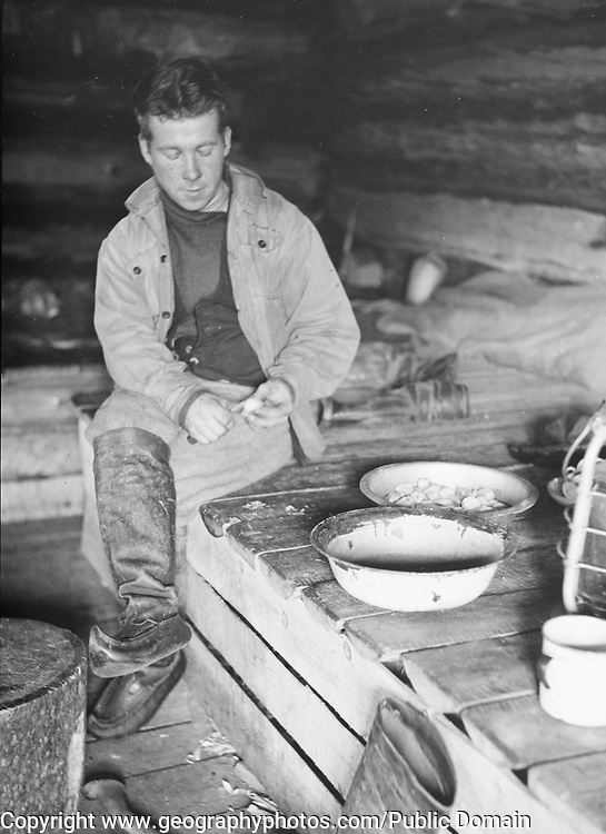 Forester peeling potatoes in cabin, Finland 1932