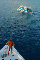 Man standing on a ship's bow looking out to sea at a Dhoni boat, Maldives.