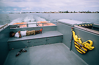 An Ebeye resident rests on the back of the ferry while travelling to Kwajalein Island. Only a small percentage of Ebeye's population work at the U.S. base most of Ebeye's population do not have access to the base.