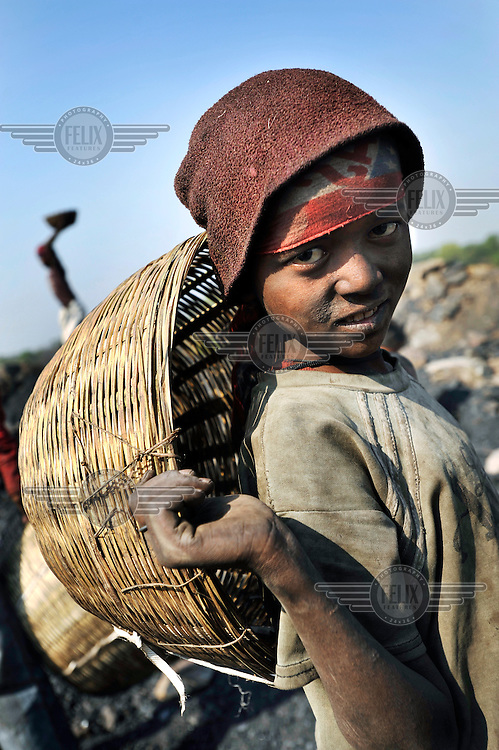 A boy holds a basket which will be filled with coal scavenged from among the waste deposits of an open cast mine. Many villagers survive by selling coal that has been illegally collected.