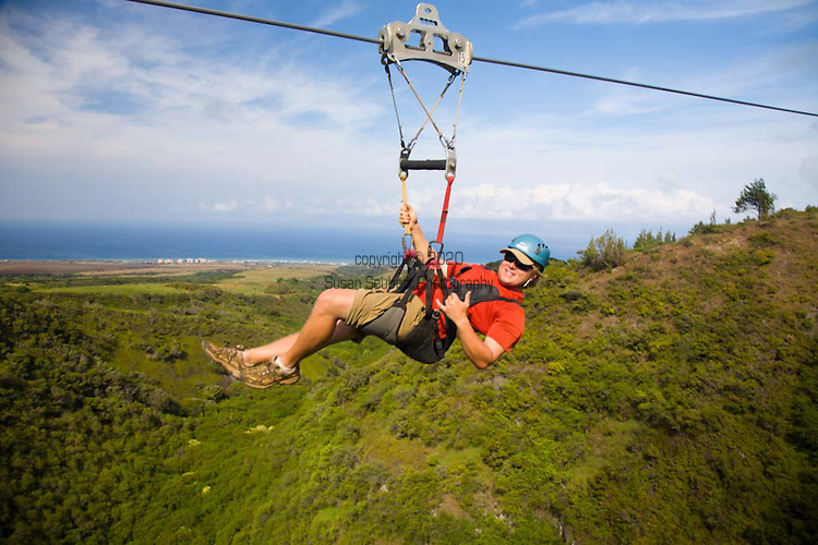 Part of the 2-mile zipline course on the slope of Mauna Kahalawai, one of the longest ziplines in the world.  Molokai and the ocean are visible in the distance as you zip from point to point over the valleys below.