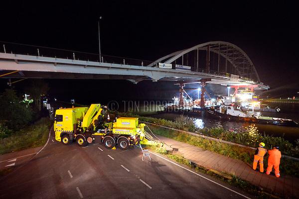 WEESP - In het holst van de nacht heeft transportspecialist Ale uit Breda de door ingenieursbureau Movares ontworpen en door bouwcombinatie KWS-Mercon gebouwde stalen Weesperbrug tussen de landhoofden over het Amsterdam-Rijnkanaal gelegd. De prefab in Gorinchem opgebouwde stalen boogbrug, is één van de vijf nieuwe bruggen die in opdracht van Rijkswaterstaat's project Kargo gebouwd worden, ter vervanging van verouderde bruggen en ter verhoging van de doorvaarthoogte voor vierlaagse containerschepen. De oude brug is eerder afgevoerd voor demontage. COPYRIGHT TON BORSBOOM
