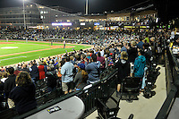 "Fans of the Columbia Fireflies applaud the singing of ""God Bless America"" in the home opener against the Greenville Drive on Thursday, April 14, 2016, the team's first day at the new Spirit Communications Park in Columbia, South Carolina. The Mets affiliate moved to Columbia this year from Savannah. Columbia won, 4-1. (Tom Priddy/Four Seam Images)"