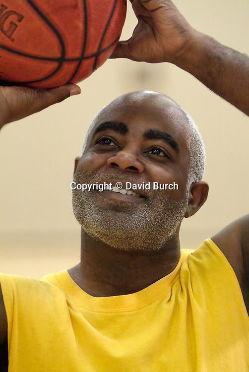 African American man shooting basketball in gym