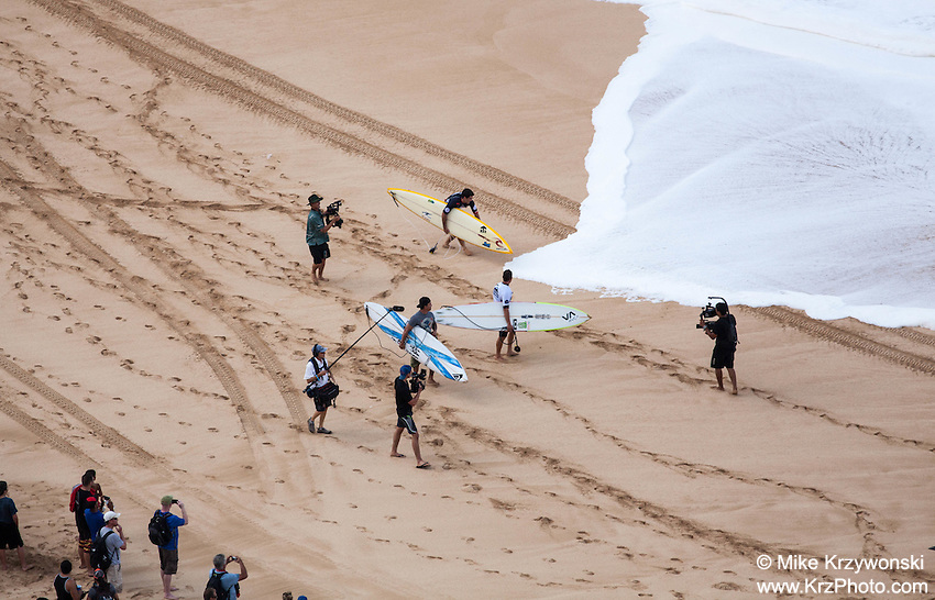 Competetors and news media at the shore just before paddling out at the 2016 Big Wave Eddie Aikau Contest, Waimea Bay, North Shore, Oahu